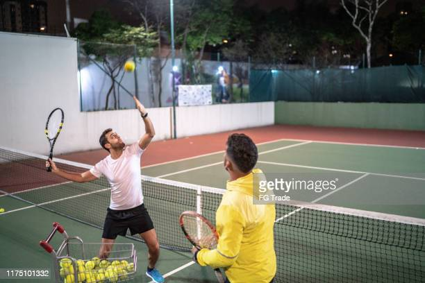 enseñar a un chico a jugar al tenis - campamento de entrenamiento deportivo fotografías e imágenes de stock