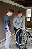 father teaches his teen son bike