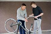 father teaches his teen son bike