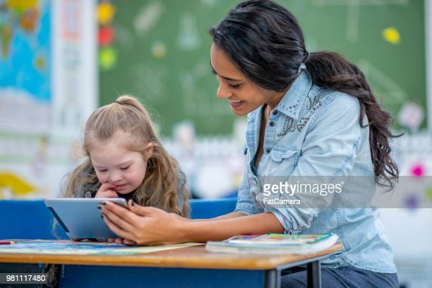 teaching elementary school girl with a tablet - assistant stock pictures, royalty-free photos & images
