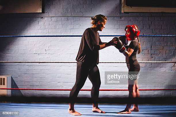 teaching her to fight! - girl fight stock photos and pictures