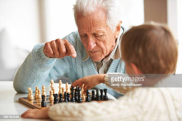 teaching his grandson about chess - chess stock pictures, royalty-free photos & images