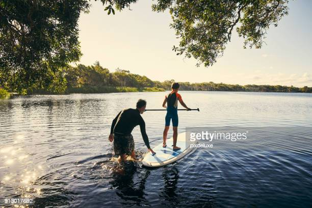 teaching my boy how to paddle - lago imagens e fotografias de stock