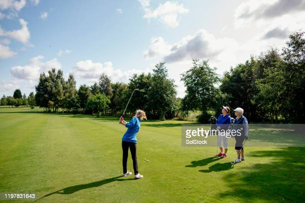 teaching showing senior students her technique - golf stock pictures, royalty-free photos & images