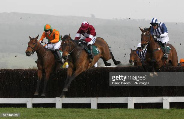 Teaforthree ridden by J T McNamara clears a fence on the way to winning the Diamond Jubilee National Hunt Chase alongside Four Commanders ridden by...