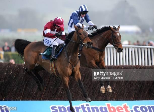Teaforthree ridden by jockey John Thomas McNamara jumps the last alongside Four Commanders ridden by jockey Nina Carberry on the way to victory in...