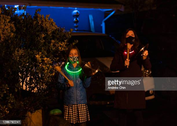 Teagan Ennis-Colliar and mother Lynn Colliar, wearing protective face masks, are seen banging on lids at 7:00 p.m. In front of their home in support...