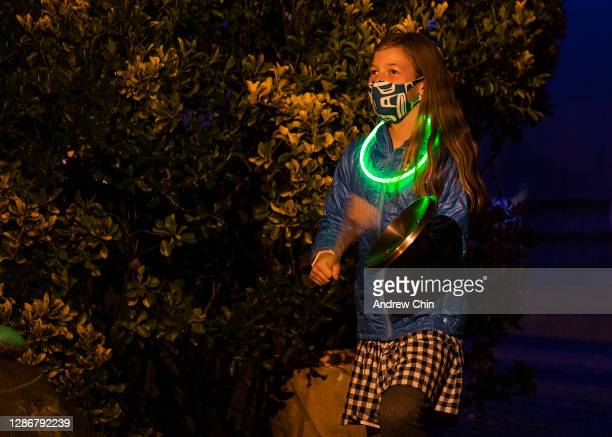 Teagan Ennis-Colliar, wearing a protective face mask, is seen banging on lids at 7:00 p.m. In front of her home in support of health workers on...