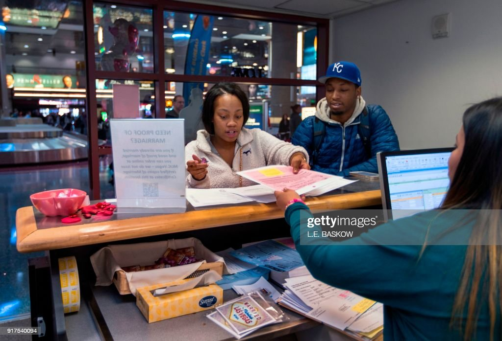 Teaira Thompson and James Anderson of Burlington, Iowa, complete their paperwork as the Clark County Clerk's Office operates a temporary pop-up marriage license office at McCarran International Airport in Las Vegas on February 12, 2018. The Las Vegas airport has given new meaning to rushing to make a connection, offering quickie wedding licenses for lovebirds desperate to get hitched on Valentine's Day. Clark County, the authority that administers Sin City's weddings, has opened a pop-up marriage license bureau by a baggage carousel at McCarran International Airport. E. Baskow / TO GO WITH AFP STORY, 'Valentines get quickie marriage licenses at Las Vegas airport'