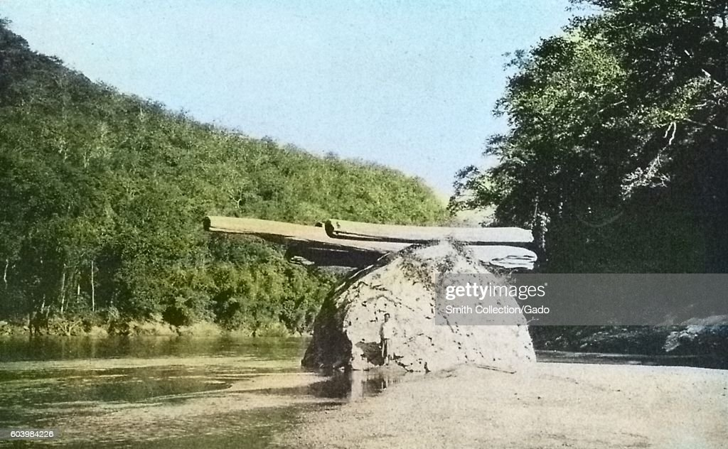 Teak log stranded on a rock in the Meh Ping river, showing the height the river attains in the rainy season, Thailand, 1922. Note: Image has been digitally colorized using a modern process. Colors may not be period-accurate. (Photo by Smith Collection/Gado/Getty Images).