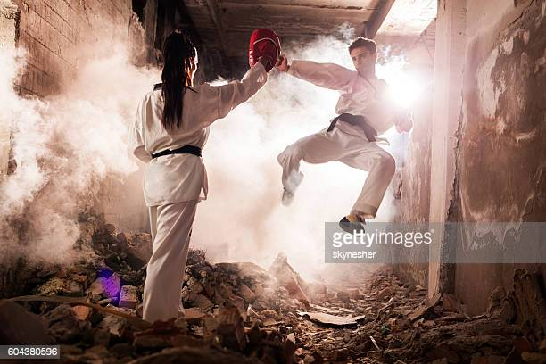 Teakwondo fighter practicing jump kick with his sparing partner.