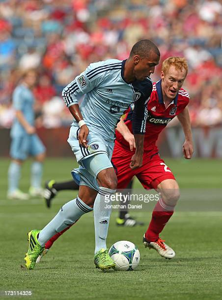 Teal Bunbury of Sporting Kansas City moves against Jeff Larentowicz of the Chicago Fire during an MLS match at Toyota Park on July 7 2013 in...