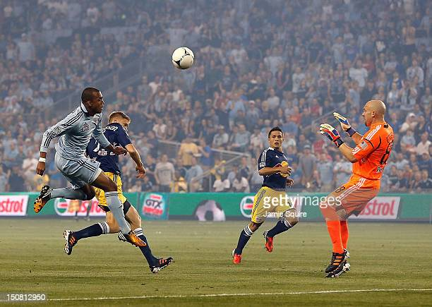 Teal Bunbury of Sporting KC kicks the ball over the head of goalkeeper Bill Gaudette of the New York Red Bulls to Kei Kamara who scored a goal during...