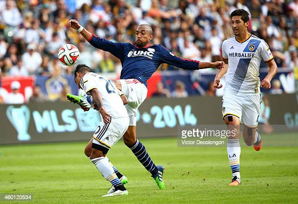 Teal Bunbury of the New England Revolution and AJ DeLaGarza of the Los Angeles Galaxy vie for the ball in the second half during 2014 MLS Cup at...