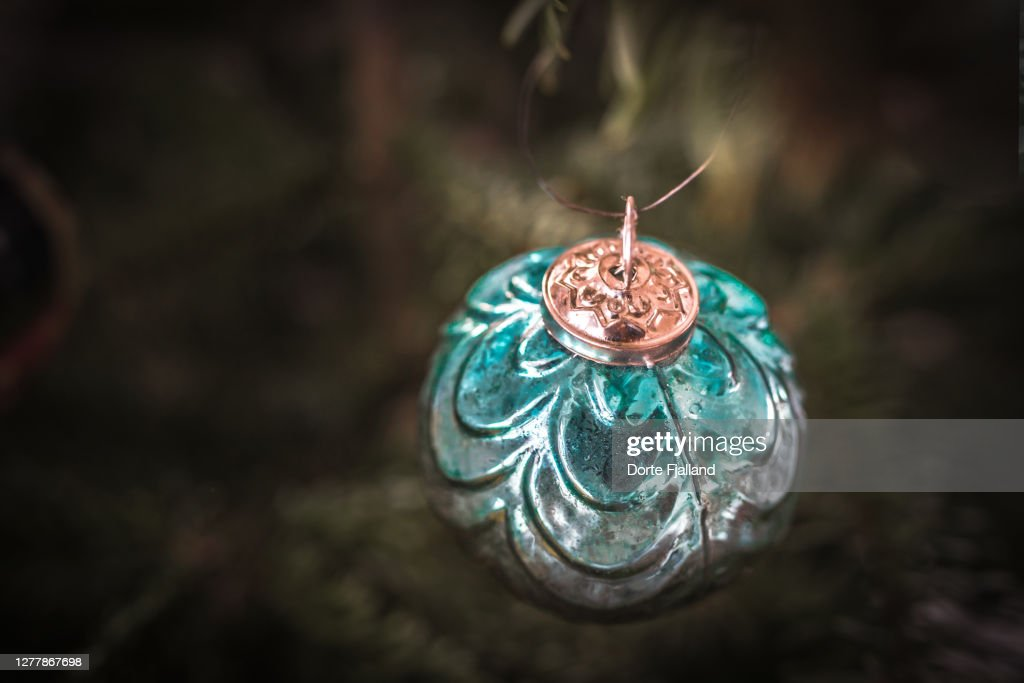 Teal green Christmas bauble with green blurred background : Foto de stock