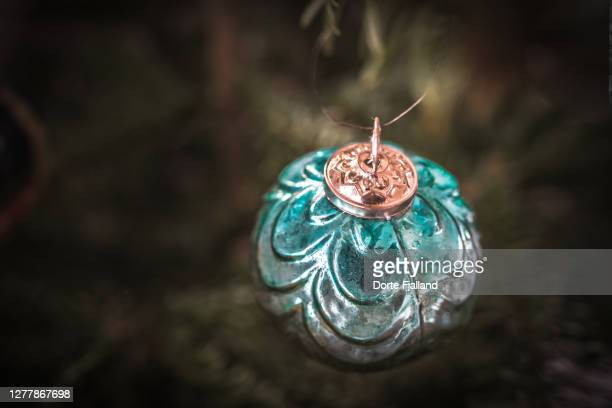 teal green christmas bauble with green blurred background - dorte fjalland fotografías e imágenes de stock