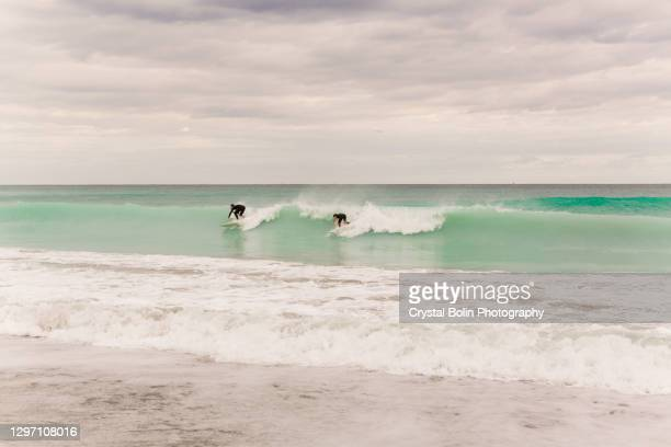 teal ocean waves sweeping across the juno beach, florida seashore at mid-day in january of 2021 - juno beach florida stock pictures, royalty-free photos & images