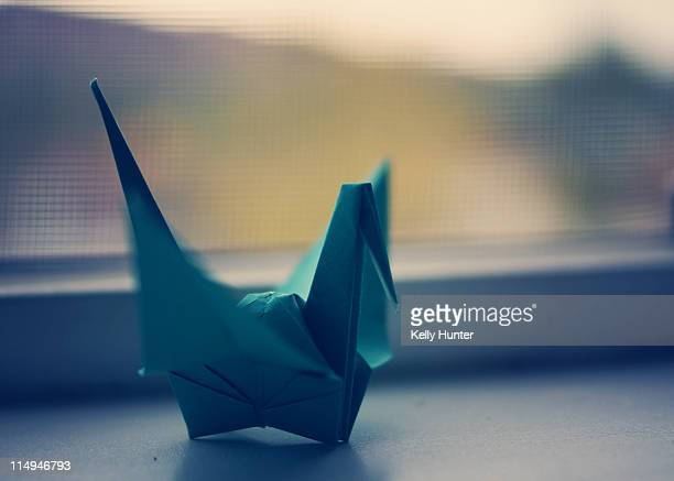 Teal peace crane by window