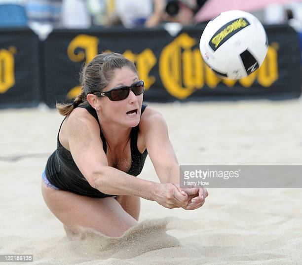 Tealle Hunkus digs a ball in a match with teammate Heather Lowe against Chelsea Hayes and Mariko Coverdale during the Manhattan Beach Open at...