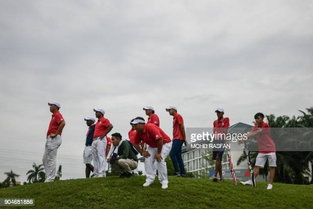 Team Asia players watch their team members playing on the 17th hole during the singles matches of the 2018 Eurasia Cup Golf tournament at the...
