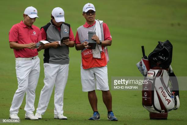 Team Asia's SungHoon Kang of Korea and Poom Saksansin of Thailand look at their scorecards during the fourball matches of the 2018 Eurasia Cup Golf...