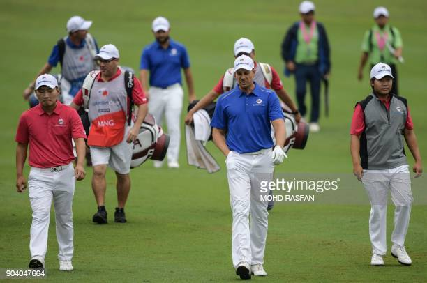 Team Asia's SungHoon Kang of South Korea and Poom Saksansin of Thailand walk with Team Europe's Henrik Stenson of Sweden during the fourball matches...