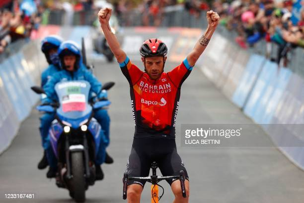 Team Bahrain rider Italy's Damiano Caruso celebrates as he crosses the finish line to win the 20th stage of the Giro d'Italia 2021 cycling race,...