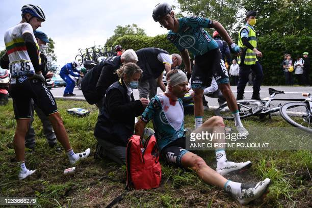 Team B&B KTM's Cyril Lemoine of France is helped by medical staff members after crashing during the 1st stage of the 108th edition of the Tour de...