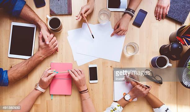 team brainstorming, high angle view on the table - conferentietafel stockfoto's en -beelden