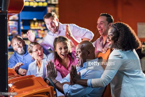team building at amusement arcade, playing racing game - arcade stock photos and pictures