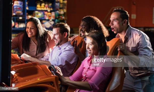 team building at amusement arcade, playing racing game - businesswear stock pictures, royalty-free photos & images