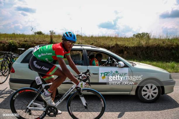 Team Burkina Faso rider Paul Daumont cycles along the team car during a stage of the 2018 edition of La Tropicale Amissa cycling race on January 16...