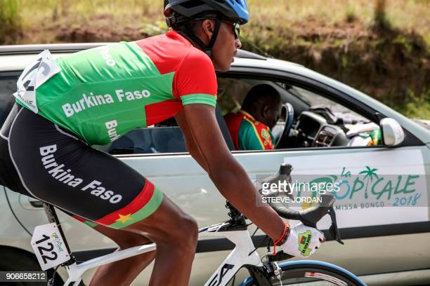 Team Burkina Faso rider Paul Daumont rides with the team car during a stage of the 2018 edition of La Tropicale Amissa cycling race on January 16...