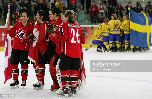 Team Canada celebrates after receiving the gold medal as silver medal winners, Sweden, celebrate together behind them after Canada defeated Sweden...