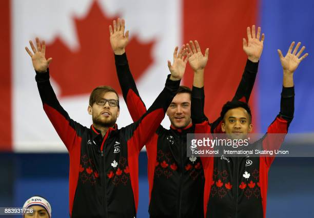 Team Canada members Laurent Dubreuil Vincent De Haitre and Gilmore Junio celebrate their first place finish and new world record in the team sprint...