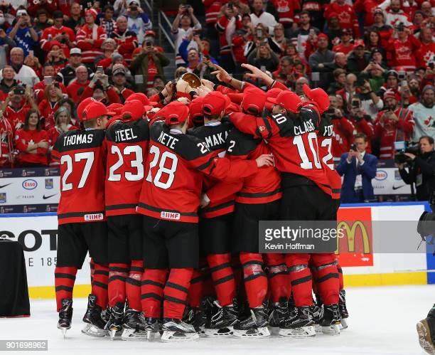 Team Canada surrounds captain Dillon Dub of Canada as he holds the trophy after the Gold medal game against Sweden of the IIHF World Junior...