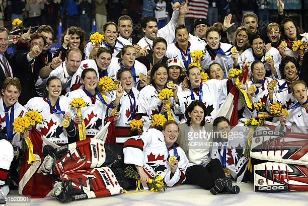 Team Canada with head coach Daniele Sauvageau celebrate following their 3-2 gold medal winning performance over the USA in the Women's Ice Hockey...