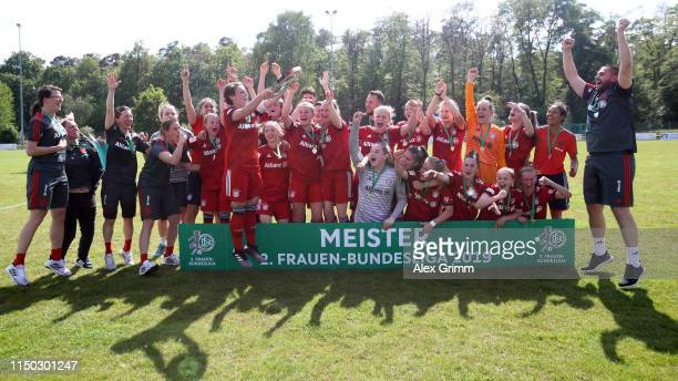 Team captain Anja Pfluger and players of Muenchen celebrate with the trophy after winning the title after the 2 Frauen Bundesliga match between TSG...