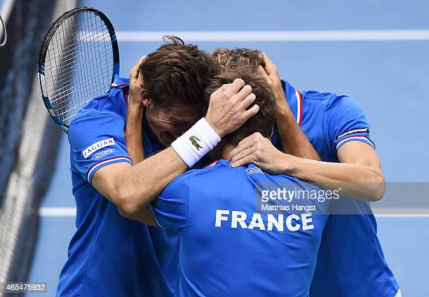 Team captain Arnaud Clement of France celebrates with Julien Benneteau and Nicolas Mahut of France after winning their match against Benjamin Becker...