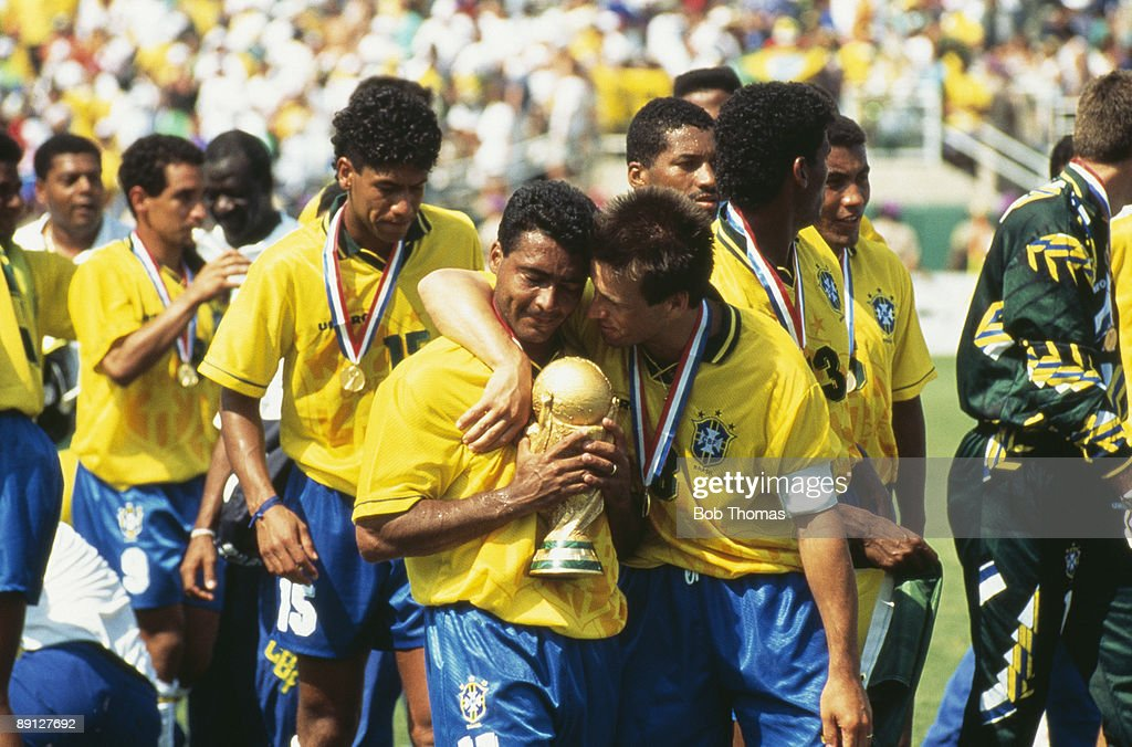 Team captain Dunga puts his arm around Romario, who is holding the FIFA World Cup Trophy, after Brazil beat Italy 3-2 on penalties in the final of the World Cup, at the Rose Bowl, Pasadena, Los Angeles County, California, 17th July 1994.
