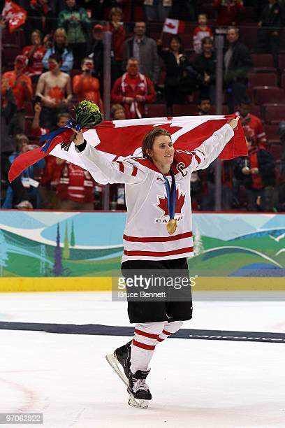 Team captain Hayley Wickenheiser of Canada celebrates with her national flag after receiving the gold medal following her team's 2-0 victory during...