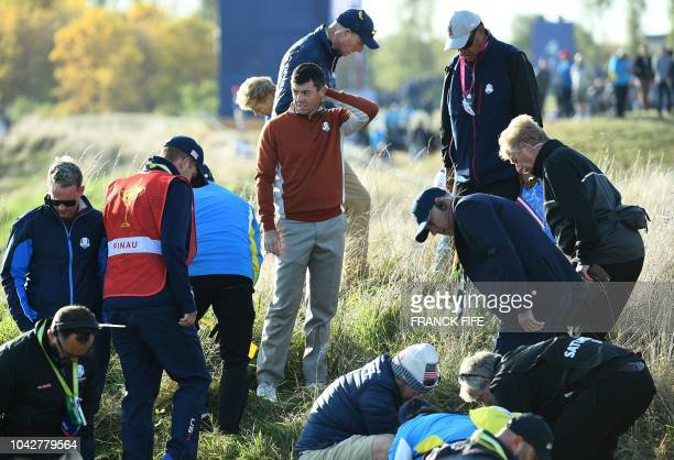 TOPSHOT US team captain Jim Furyk Europe's Northern Irish golfer Rory McIlroy and staff look for a ball the fourball matches on the second day of the...