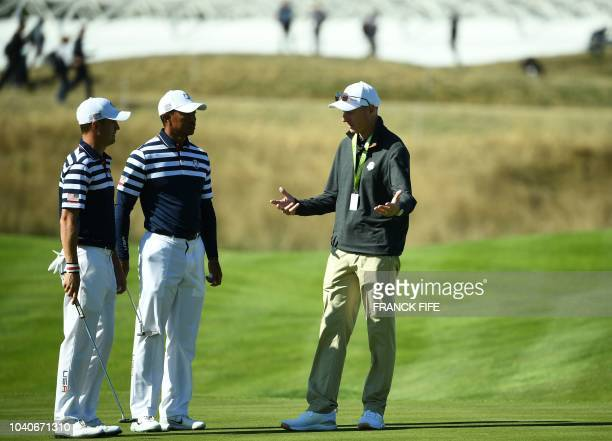 US team captain Jim Furyk speaks with US golfer Tiger Woods and US golfer Justin Thomas during a practice session ahead of the 42nd Ryder Cup at Le...
