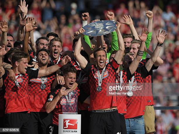 Team captain Julian Schuster of Freiburg presents the trophy for the second Bundesliga champion after the second Bundesliga match between SC Freiburg...