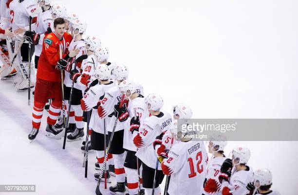 Team captain Klim Kostin of Russia shakes hands with members of team Switzerland following the bronze medal game at the IIHF World Junior...
