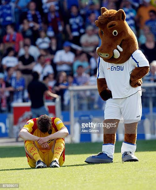 Team captain Maik Franz of Karlsruhe and mascot Willi mourn after the Bundesliga match between Karlsruher SC and Hertha BSC Berlin at Wildpark...