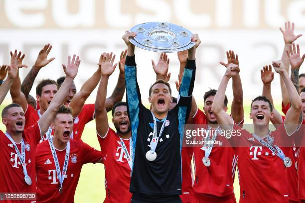 Team captain Manuel Neuer of FC Bayern Muenchen lifts the trophy to celebrate the championship following the Bundesliga match between VfL Wolfsburg...