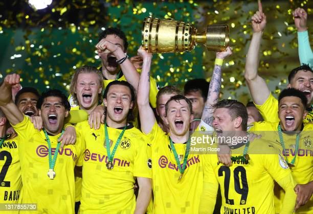 Team captain Marco Reus of Dortmund lifts the trophy as his team mates celebrate after winning the DFB Cup final match between RB Leipzig and...