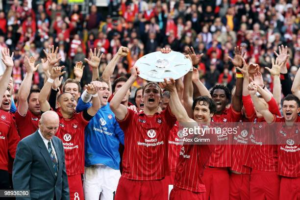 Team captain Martin Amedick of Kaiserslautern holds up the championship trophy with team mates after the Second Bundesliga match between 1. FC...