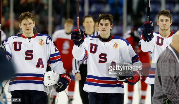 Team Captain Mikey Anderson Jack Hughes and Joel Farabee of the United States raise their sticks in celebration following a 31 quarterfinal game...